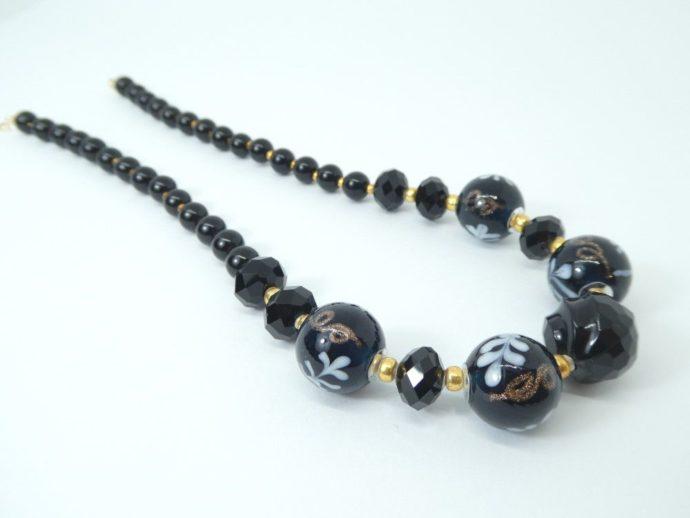 Gros plan sur les perles du collier noir et or.