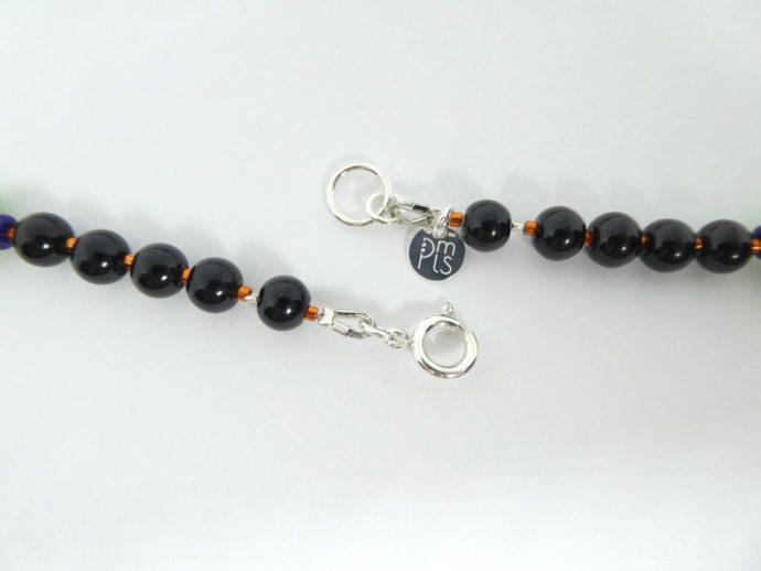 Le fermoir du collier noir vert et orange avec les perles rondes.