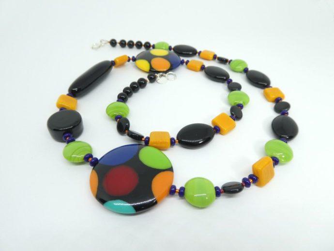 Le collier noir vert et orange a de magnifiques palets ronds en résine.