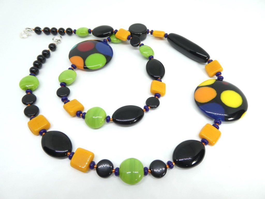 Le collier noir vert et orange et les deux grands palets ronds.