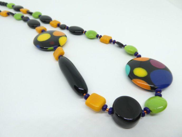 Gros plan sur les perles utilisées pour le collier noir vert et orange.