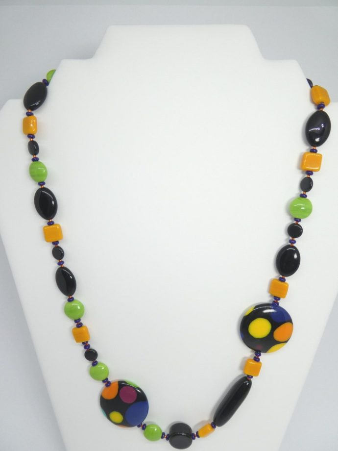 Le collier noir vert et orange sur son présentoir.