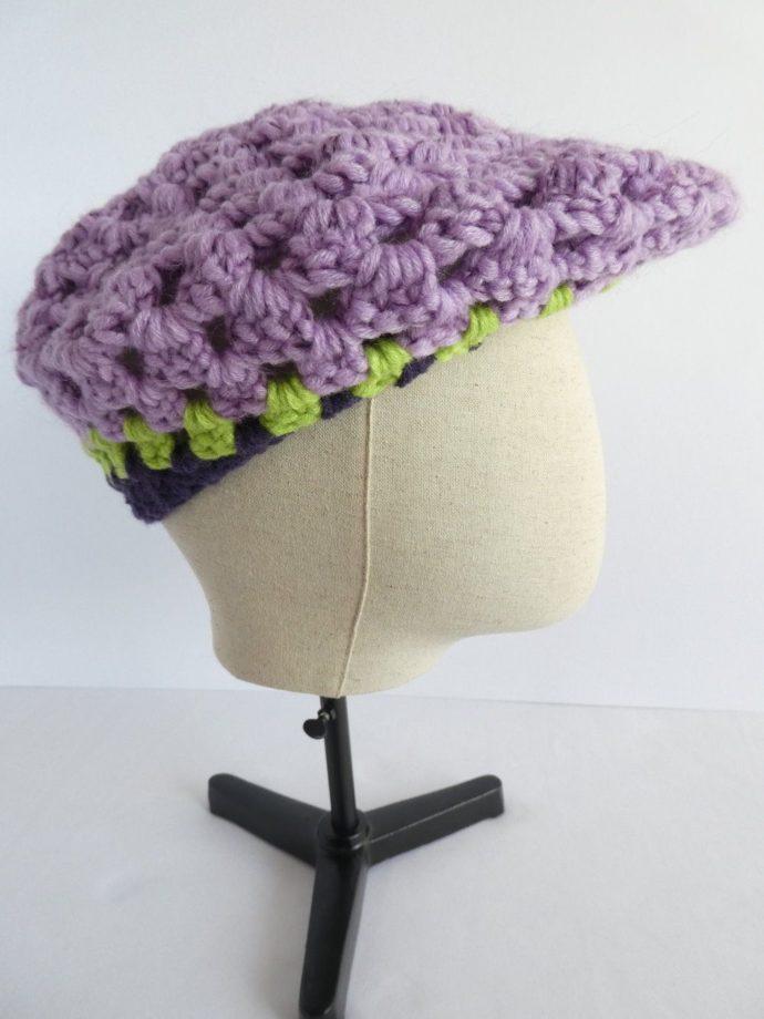 Le béret mauve en laine façon casquette.