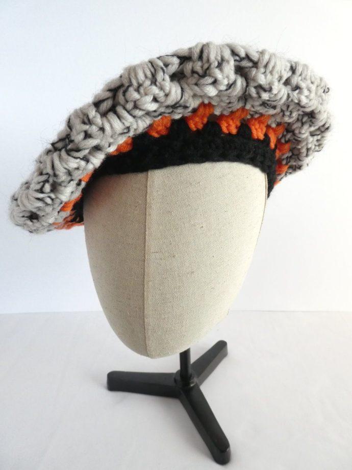 Le béret noir et blanc en laine de la boutique Pamalussi porté penché sur le côté.