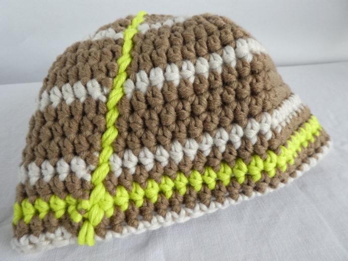 Gros plan du bonnet en laine terre et beige.