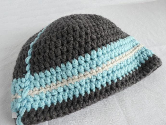 Gros plan du bonnet gris et bleu en laine.