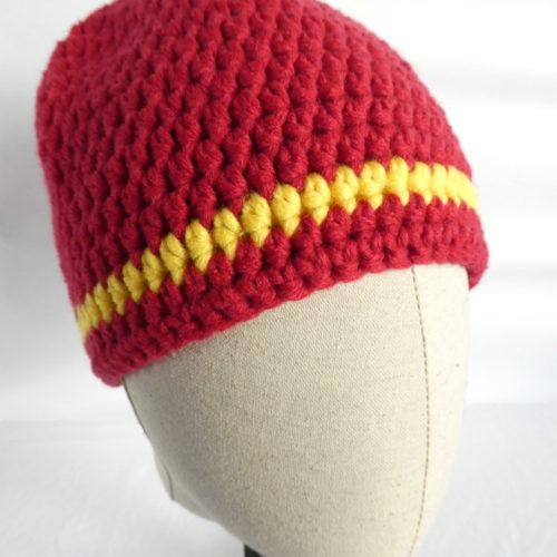 Un bonnet crocheté en laine rouge avec une rayure jaune.