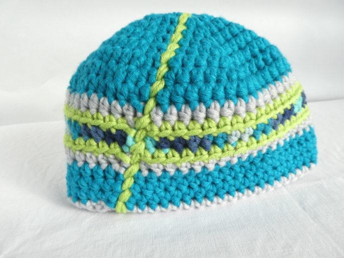 Détail de l'arrière du bonnet en laine turquoise et bleu.