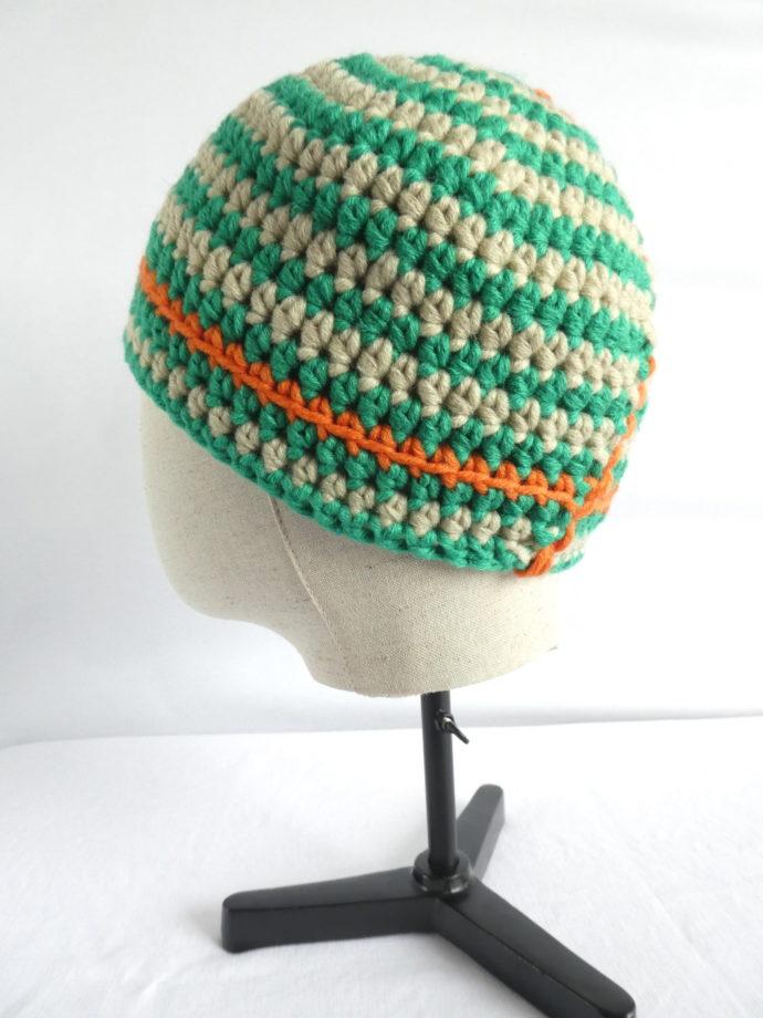 Une autre vue du bonnet vert et beige en laine.