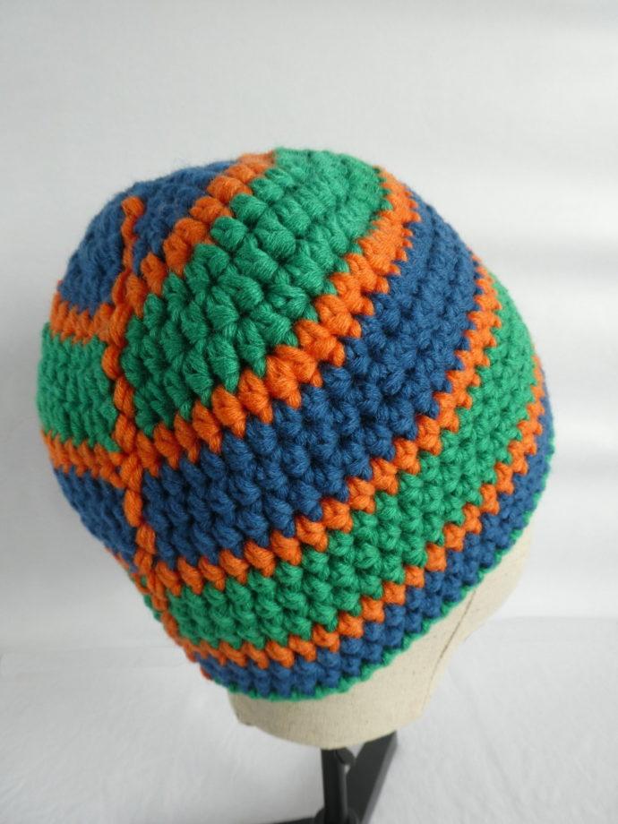 Le bonnet vert et bleu Mondeville. Il est crocheté à la main.
