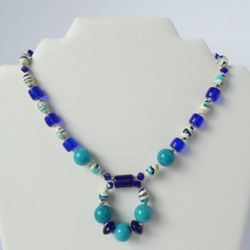 Le collier avec pendentif fixe bleu sur le présentoir.