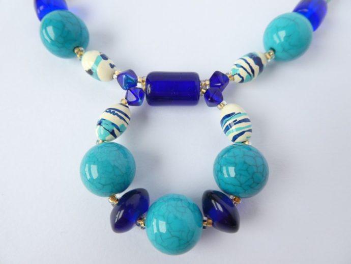 Détail du pendentif fixe du collier bleu de l'atelier Pamalussi.
