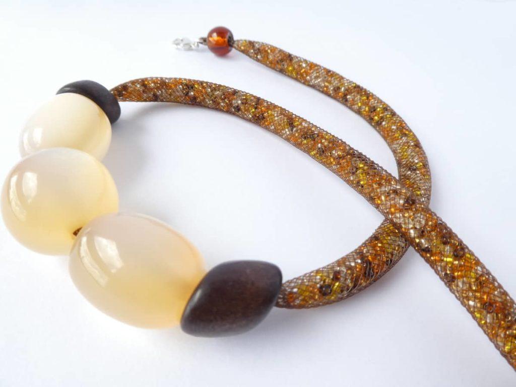 Collier en résille tubulaire marron avec trois grosses perles nacrées.