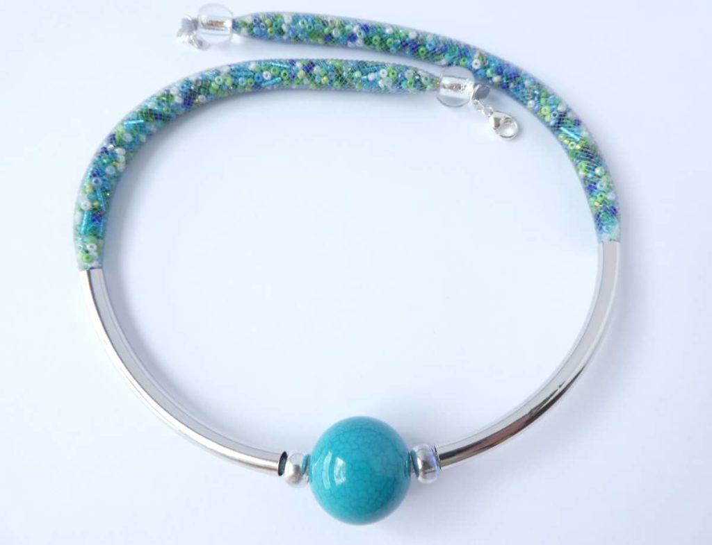 Collier en résille tubulaire grise avec grosse perle de couleur turquoise.