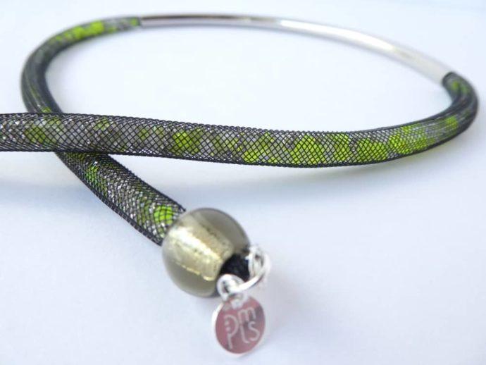 Les perles vert fluo glissées dans la résille tubulaire.