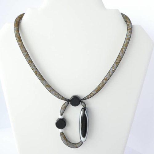 Le collier avec pendentif en résille tubulaire noire.