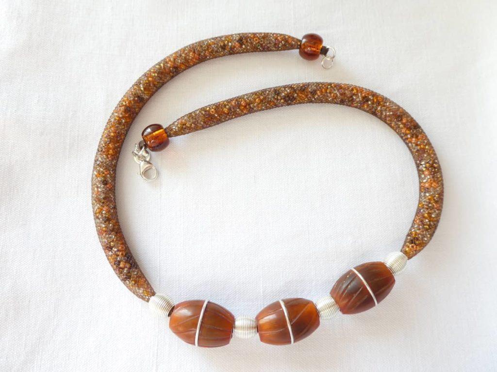 Le collier unique avec ses trois perles en résine synthétique terminé.