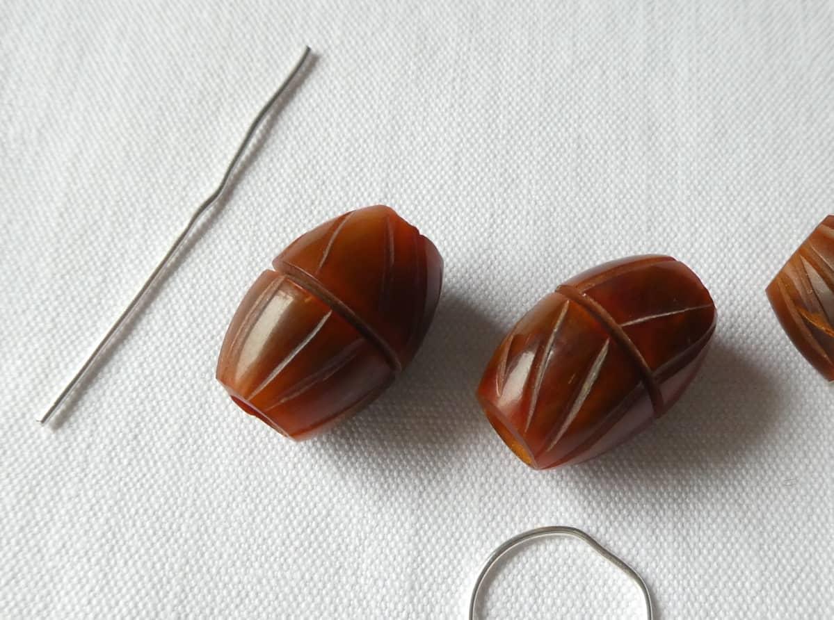 Les perles avec les rainures à combler de fil d'argent.