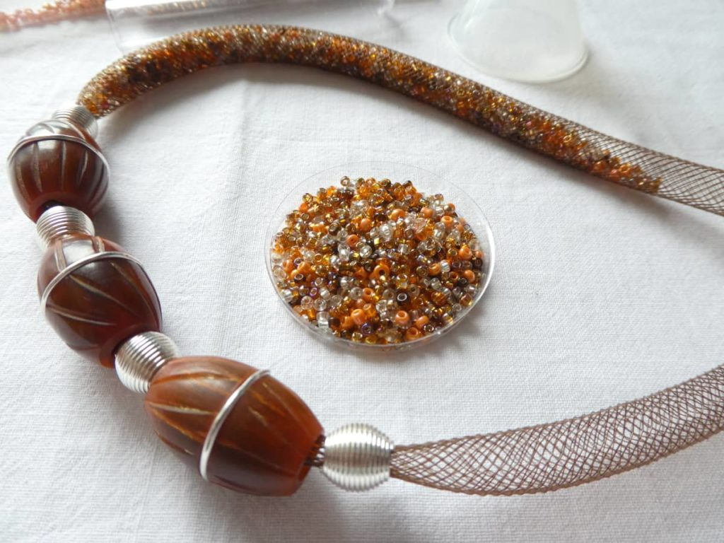 Le mélange de rocailles irisées pour remplir la résille tubulaire de ce collier unique.