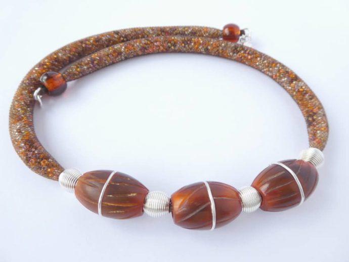 Les trois grosses perles marron et le fil d'argent incrusté dedans.