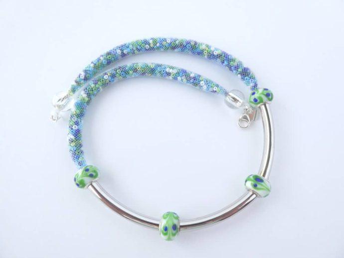 Les tubes courbés en métal argenté entourés de perles en verre genre Murano.