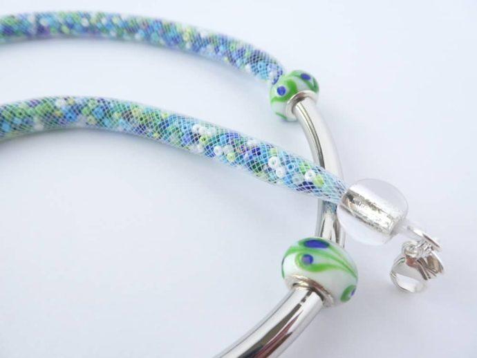 La résille blanche garnie de rocailles bleues, vertes et blanches.