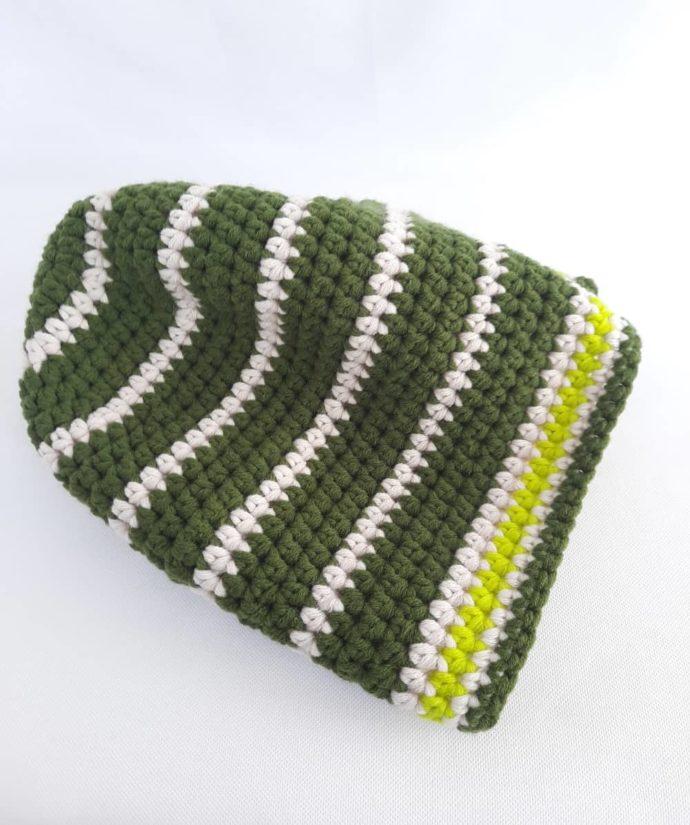 Gros plan du bonnet vert et écru en laine Huelgoat.