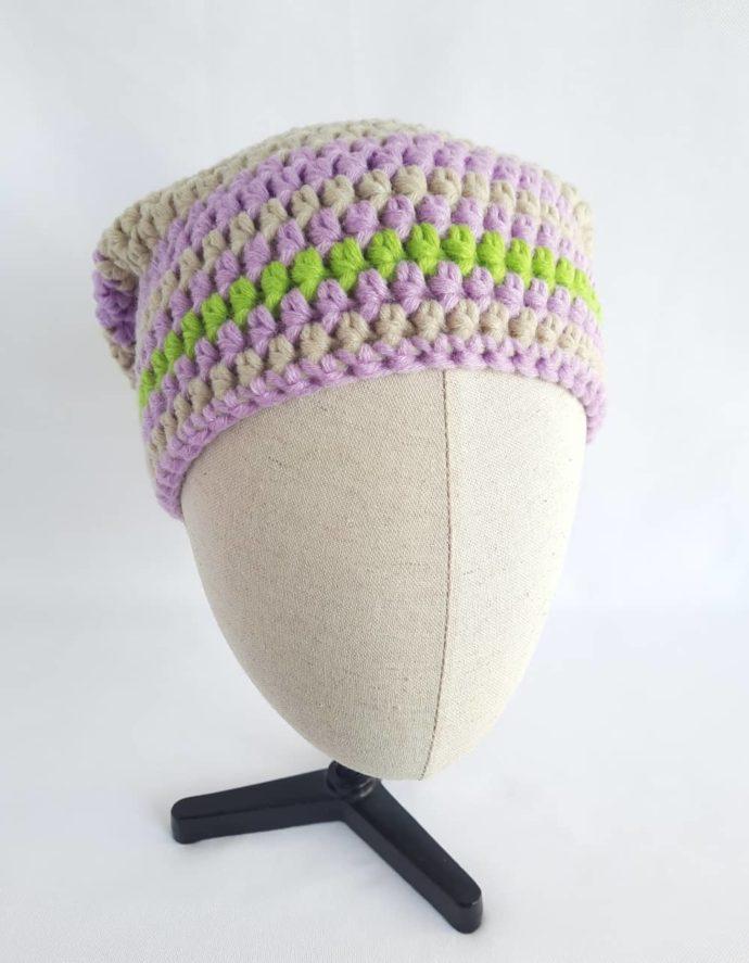 Le bonnet mauve et chanvre en laine crocheté à la main.