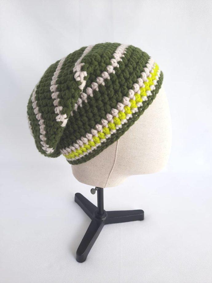Vue de profil du bonnet vert et écru en laine Huelgoat.