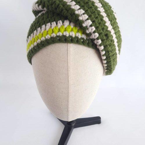 Le bonnet vert et écru en laine Huelgoat en version penchée sur le côté.