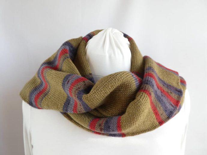 L'écharpe en laine à rayures kaki portée sur les épaules.