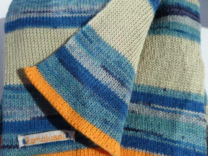 Au bord de l'écharpe en laine chanvre et bleues quelques rangs en orange.