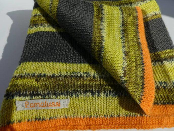 Le bord orange de l'écharpe en laine à rayures grises et vert anis.