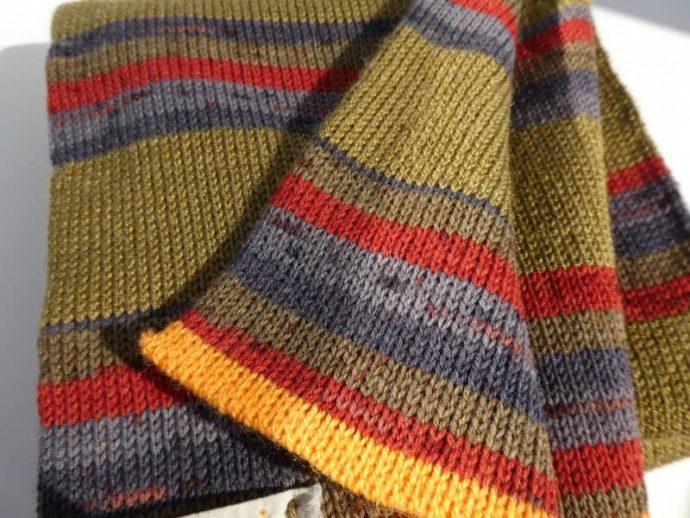 Un peu de rouge et de bleu éclaire le kaki de l'écharpe en laine fine.