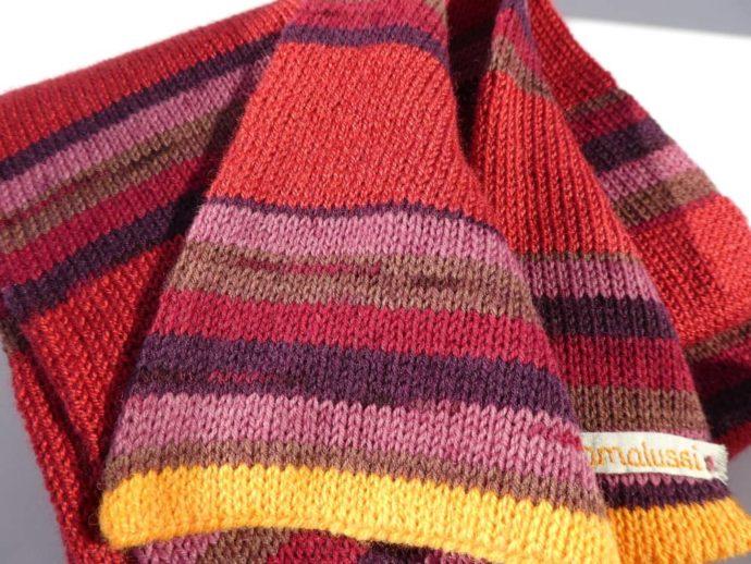 Détail des rayures rouges de l'écharpe en laine fine.