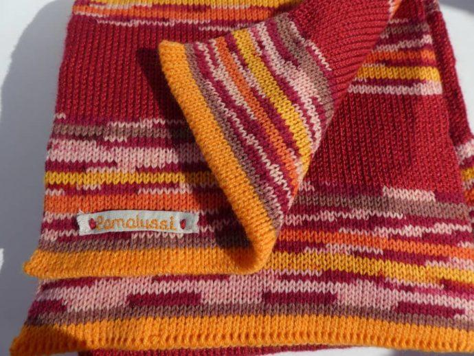 L'écharpe en laine à rayures rouges a aussi du orange, du jaune et du rose.