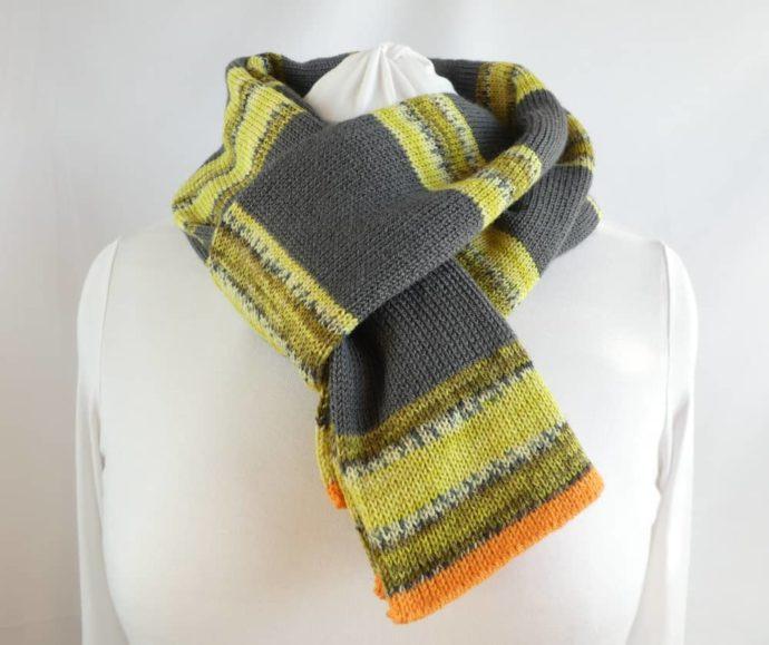 L'écharpe en laine à rayures grises et vert anis nouée autour du cou.