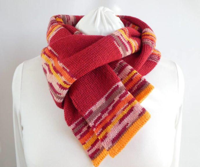 Nouée autour du cou, elle est gaie l'écharpe en laine à rayures rouges.