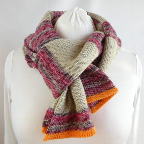 L'écharpe en laine fine à rayures chanvre et rose foncé.
