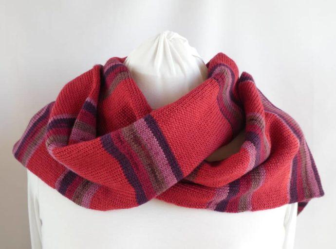 Elle peut aussi se porter sur l'épaule l'écharpe en laine à rayures rouges.
