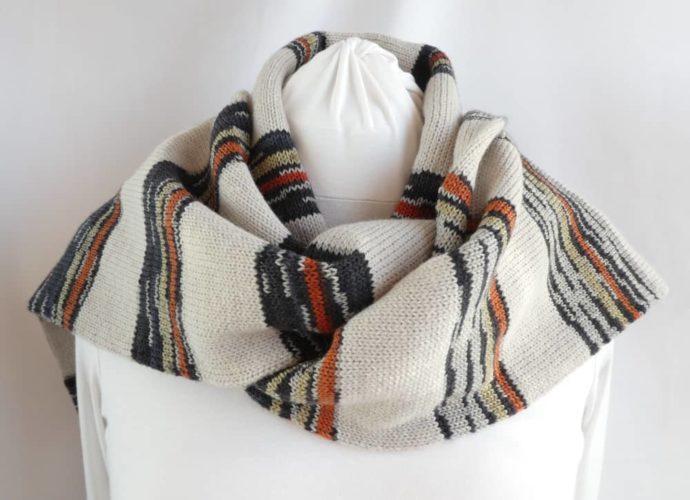 L'écharpe en laine fine à rayures chanvre et noires portée sur les épaules.