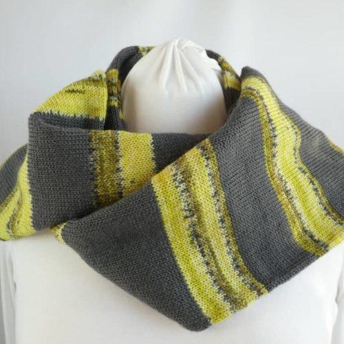 L'écharpe en laine à rayures grises et vert anis.