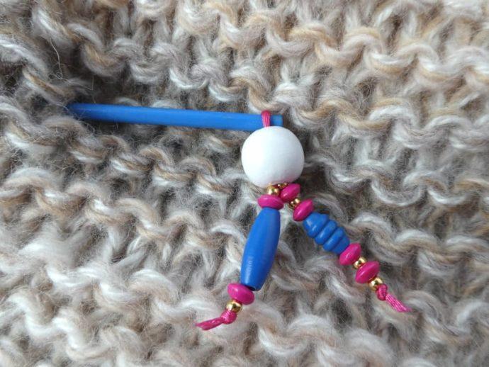 Gros plan sur les perles en bois du bijou d'écharpe bleu.