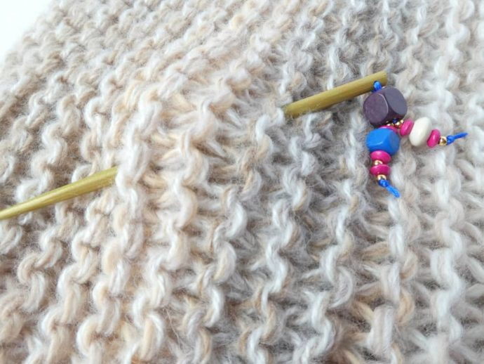 Le bijou d'écharpe or piqué dans une grosse écharpe Pamalussi.