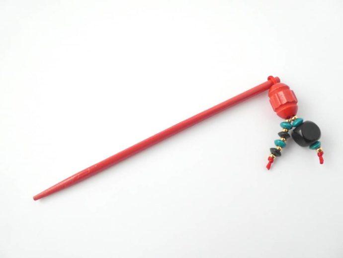 Le bijou d'écharpe de couleur rouge de l'atelier Pamalussi.