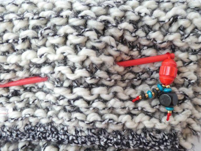 Le bijou d'écharpe rouge piqué dans une grosse écharpe Pamalussi;