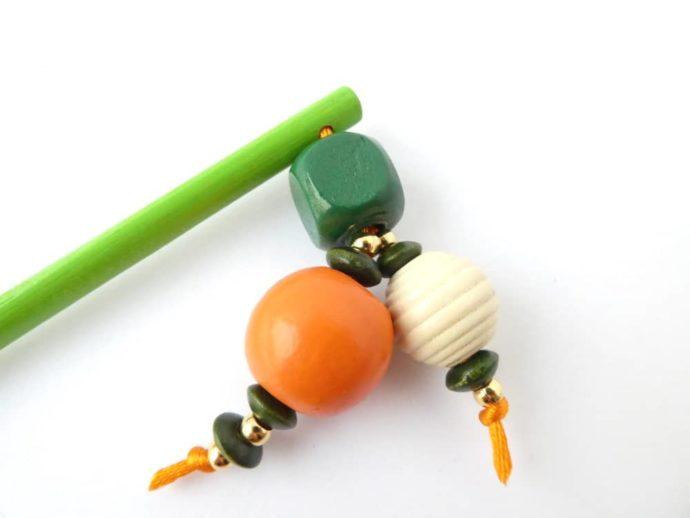 Gros plan sur les perles en bois du bijou d'écharpe vert.