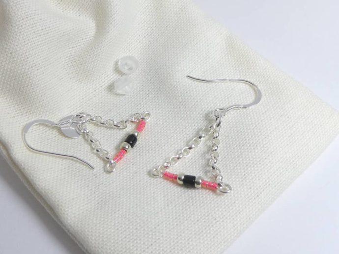 Les embouts et le pochon en coton des boucles d'oreilles roses avec chaîne argent.