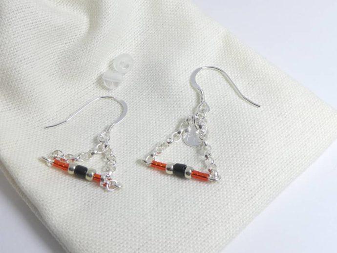 Les embouts et le pochon en coton des boucles d'oreilles rouges avec chaîne argent.