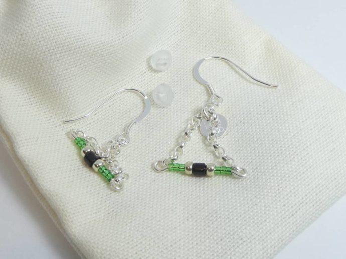 Les embouts et le pochon en coton des boucles d'oreilles vertes avec chaîne argent.